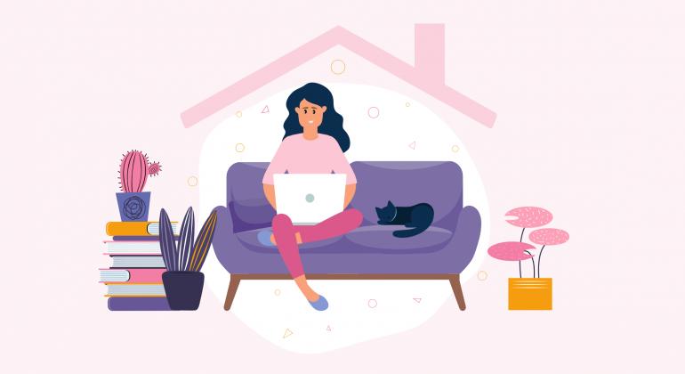 femme assise sur le canapé en travaillant à la maison avec son ordinateur portable